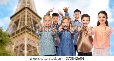 childhood, travel, tourism, gesture and people concept - happy smiling children showing thumbs up over paris eiffel tower background - stock photo