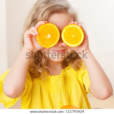 Childr with oranges. Happy little girl with fruit at home. - stock photo
