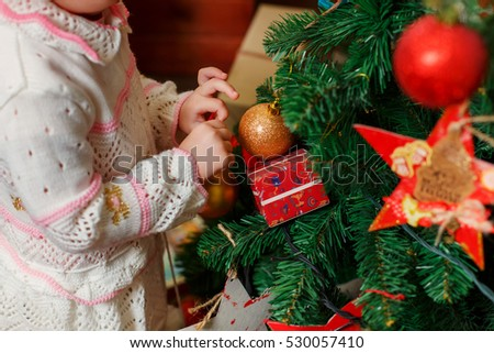 Children and Christmas. Child at Christmas. decorating a Christmas tree. girl's hands with gloves decorate the