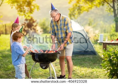 children and grandfather having a barbecue party on camping