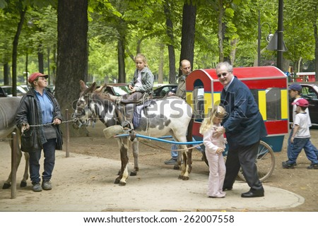 Children and parents at Donkey Ride in park, Paris, France
