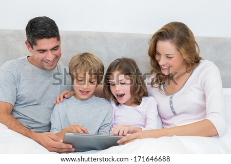 Children and parents using digital tablet in bed - stock photo