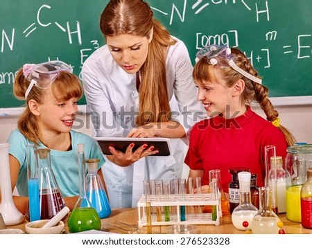 Children and teacher holding flask in chemistry class. Looking at pc. - stock photo