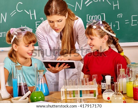 Children and teacher holding flask in chemistry class. Looking at pc. Studying chemistry at school. - stock photo