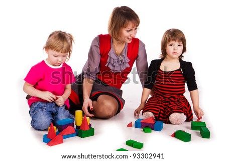 Children and their mother building a castle with cubes isolated on white