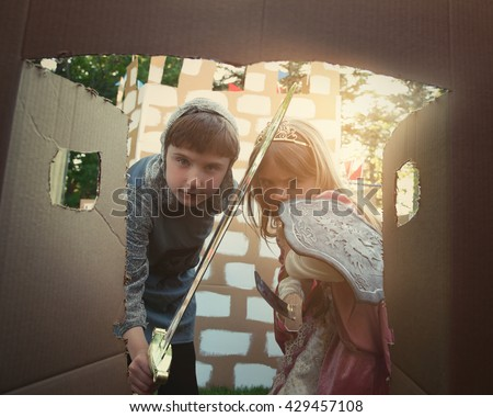 Children are dressed in a knight and princess costumes looking in a door of a cardboard castle for a creative imagination concept.