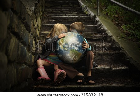 Children are holding the planet earth on wet dark stairs for a weather or season concept about the environment. Elements of this image furnished by NASA.  - stock photo