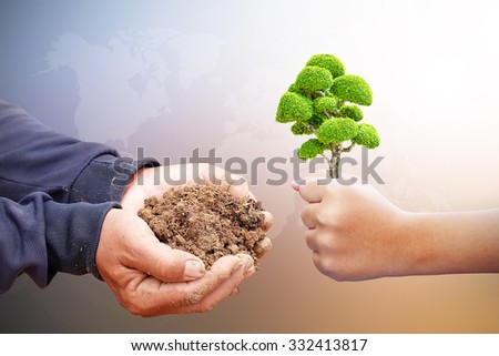 Children are holding tree To send a father to grow. Adult,father hands holding soil,Hand dirty with soil. The growth of the trees make a fertile environment. Business growth and success.