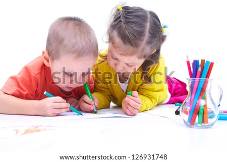 Children are laying on the floor and painting pencils - stock photo