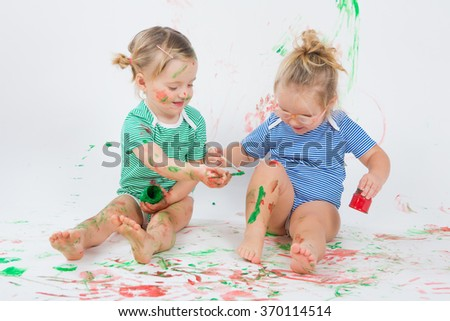 Children are painting on background and floor - stock photo