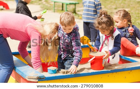 Children are playing at the playground with sand in the sandbox - stock photo