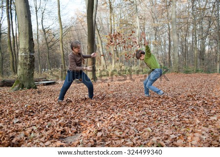 Children are playing in the forest with the leaves - stock photo