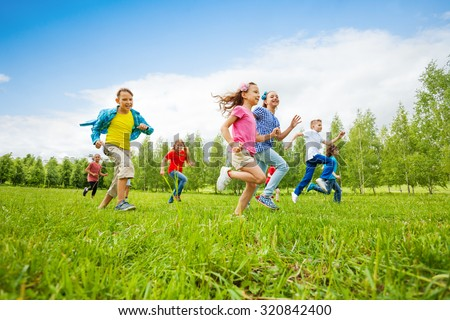 Children are running through green field together - stock photo
