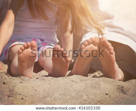 Children are sitting on a sand beach with their bare feet together for a vacation, travel or summer concept - stock photo
