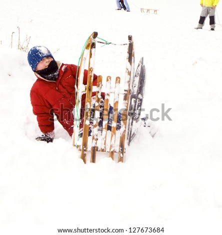 children are sledding down the hill in snow, white winter - stock photo