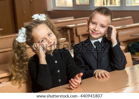 Children are speaking on the telephone at school
