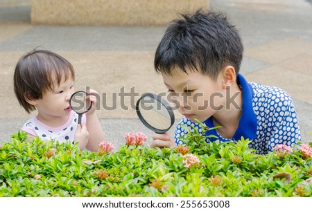 Children are using magnifying glass for exploring in garden - stock photo