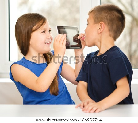 Children are using tablet and having fun while sitting at table, isolated over white - stock photo