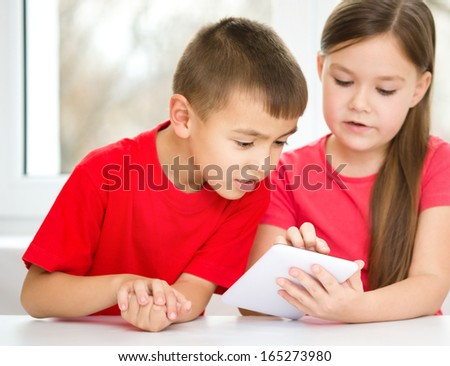 Children are using tablet while sitting at table, isolated over white - stock photo