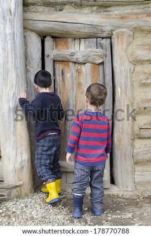 Children at a wooden barn door on a farm, back view. - stock photo