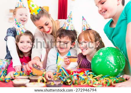 Children at birthday party grabbing muffins and cake, the kids are wearing hats, balloons and paper streamers for decoration  - stock photo