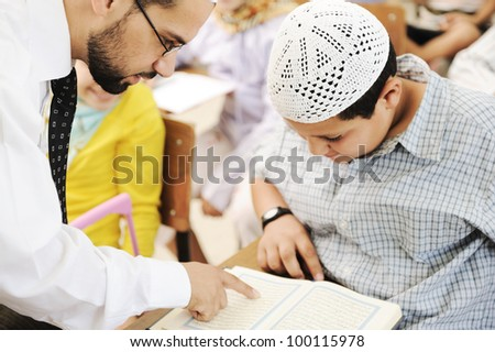 Children at school classroom, reading Koran (no copyright infringements for Koran) - stock photo