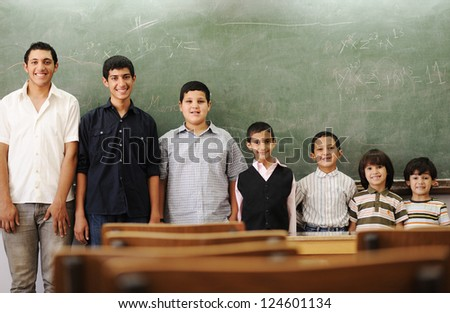 Children at school from smaller to bigger line row - stock photo