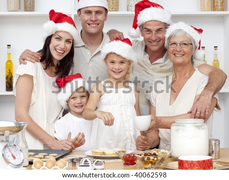 Children baking Christmas cakes in the kitchen with their parents and grandparents - stock photo