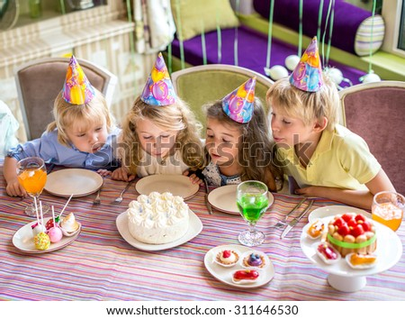 Children blow out the candles on the cake