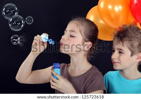 Children blowing bubbles - stock photo