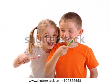 Children, boy and girl brush their teeth with toothbrushes and laugh, isolated on white - stock photo