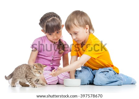 children boy and girl feeding cat kitten - stock photo
