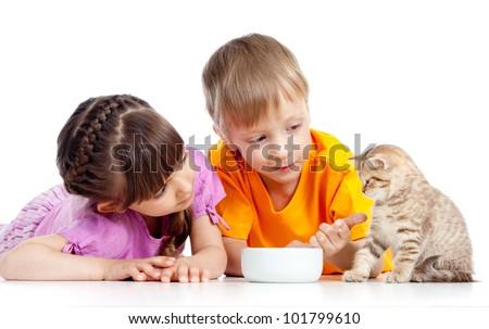 children boy and girl feeding kitten - stock photo