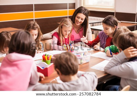 Children boys and girls sitting together around the table in classroom and drawing. With them is their young and beautiful teacher.  - stock photo