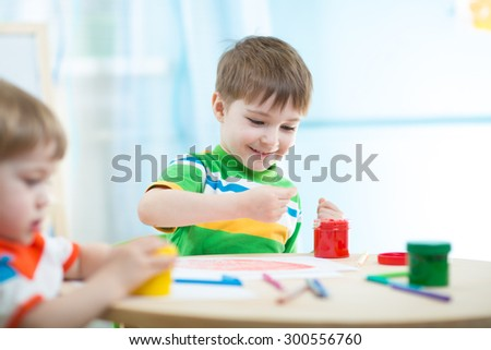 children boys painting in daycare or nursery or playschool - stock photo