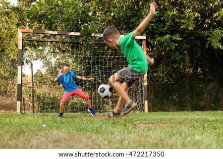 Children boys playing football in park