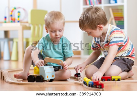 Children boys playing railroad  together in playroom - stock photo