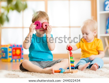children boys playing with educational toys indoors - stock photo