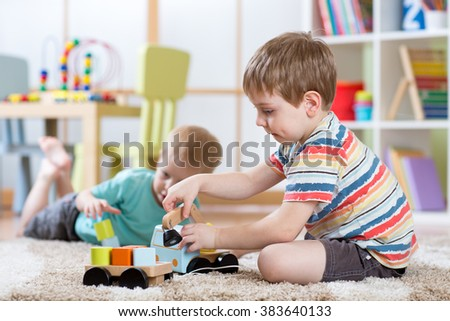 children boys toddlers playing with toy car indoors