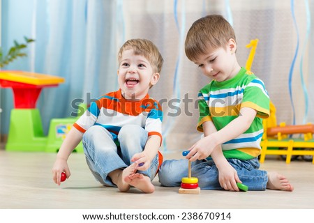 children boys with educational toy in playroom - stock photo