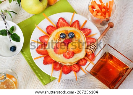 Children breakfast pancakes smiling face of the sun lion strawberry blueberry and apricot, cute food, honey, creative idea for kids - stock photo