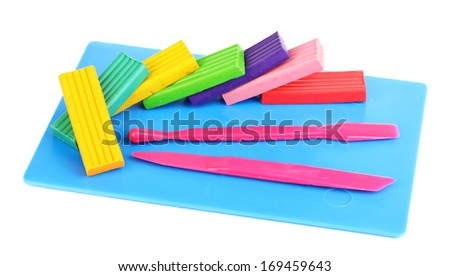 Children bright plasticine on desk with stacks isolated on white