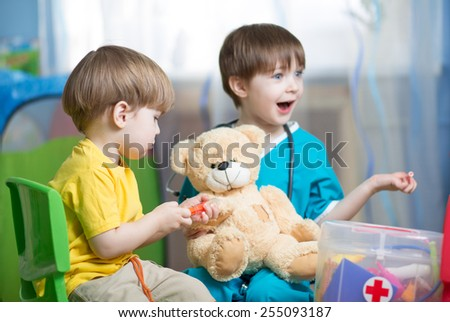 children brothers play doctor with plush toy at home