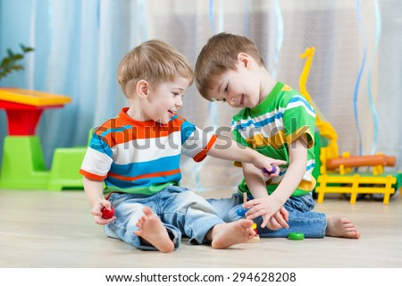 children brothers play together in nursery  or day care - stock photo