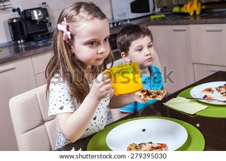 Children captivated by a TV show while eating