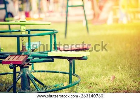 children carousel in playground. Vintage filter. - stock photo