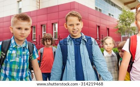 Children carry rucksacks and walk near school - stock photo