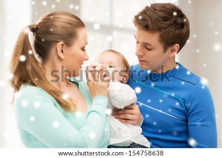 children, christmas, x-mas, love concept - happy family and adorable baby with feeding-bottle - stock photo