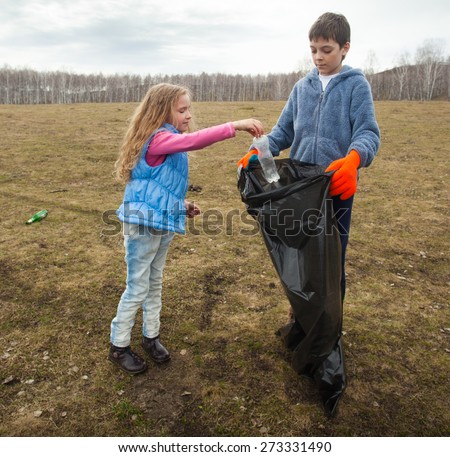 Children cleaning scavenge. Children collect garbage bag in the woods - stock photo