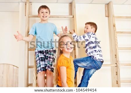 Children climbing wall bars in a school gym - stock photo